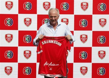 Former England manager Eriksson holds his jersey after a news conference at a stadium in Bangkok